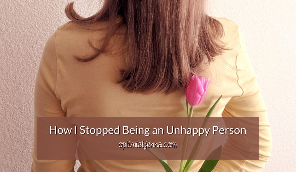 Jenna Breunig holding a tulip with the words how I stopped being an unhappy person